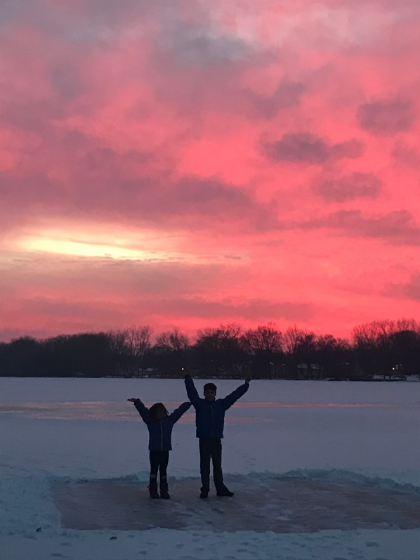 Kids playing on a frozen lake in the setting sun